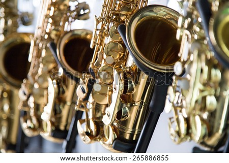 Saxophones hang at the stand - stock photo