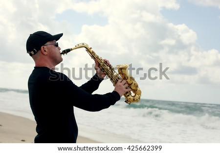 Saxophonist playing on saxophone outdoor - stock photo