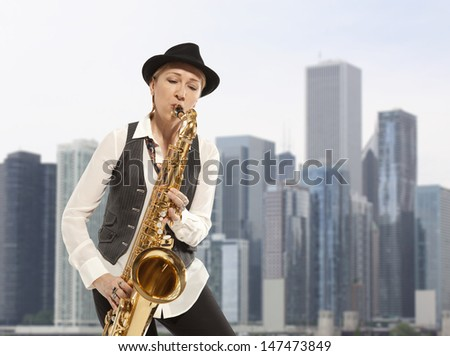 Saxophonist. Woman playing on saxophone against the background of skyscraper - stock photo