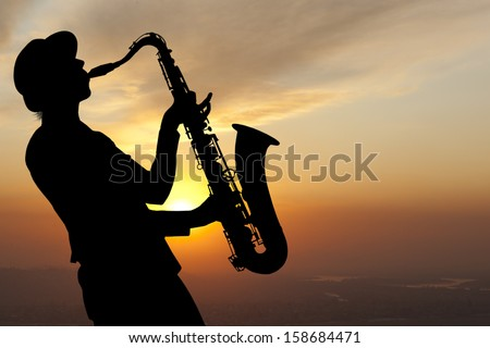 Saxophonist. Woman playing on saxophone against the background of sunset - stock photo