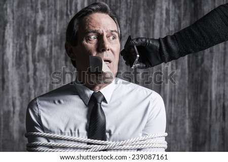 Say a few words to your nearest! Tied up businessman sitting in front of the dirty wall while someone stretching out hand with mobile phone  - stock photo