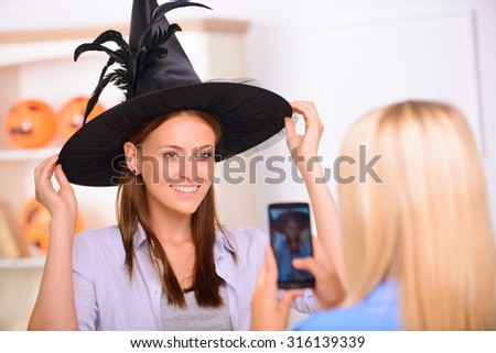 Say cheese. Nice positive beautiful girl touching her hat and having Halloween party while posing in front of the camera