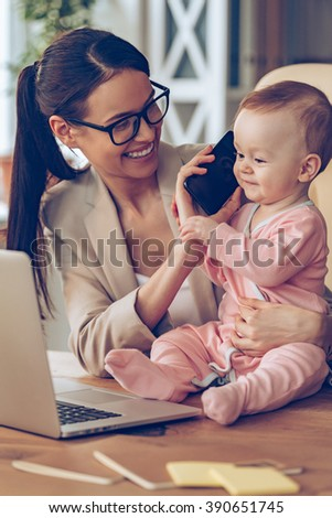 Say hello to dad! Little baby girl talking on mobile phone while sitting on office desk with her mother in office - stock photo
