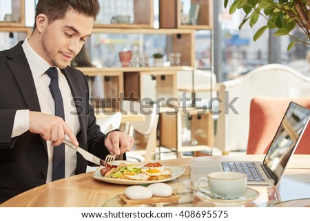Say no to hunger. Horizontal shot of a handsome cheerful businessman enjoying his lunch at the local restaurant - stock photo