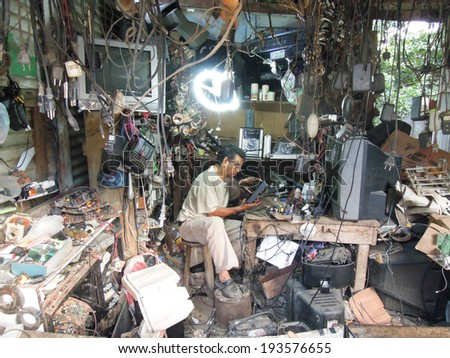 Sayaxche, Guatemala, 1 February 2014: ripairman of household appliances on his workshop at Sayaxche on Guatemala