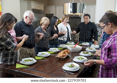 saying grace at meal / a family get together / everyone holds hands - stock photo