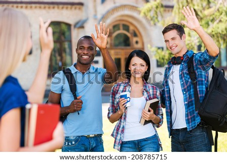 Saying hi to friends. Rear view of young woman holding books and waving to her friends standing outdoors  - stock photo