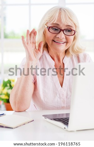 Saying hi to her nearest. Cheerful senior woman waving with her hand while looking at laptop