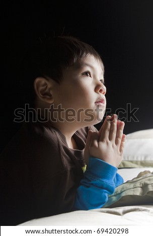 Saying his prayers before bed. - stock photo