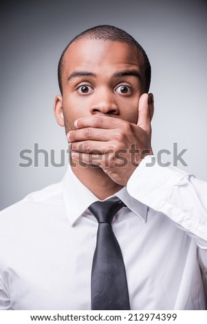 Saying no evil. Shocked young African man in shirt and tie covering mouth with hand while standing against grey background - stock photo