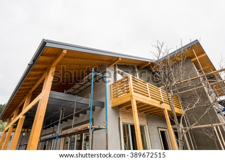 Scaffolding at the construction site of a new wooden house - stock photo