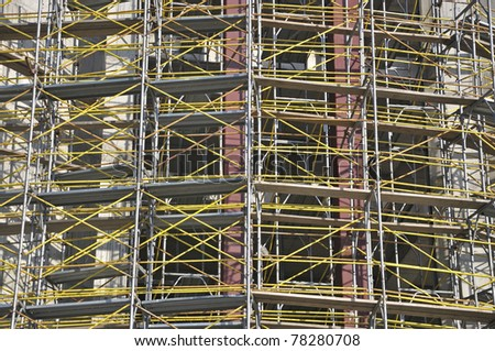 Scaffolding at the  construction site useful for background - stock photo