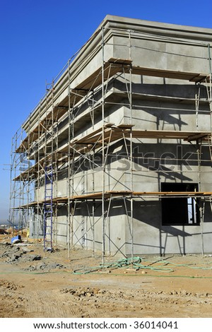 Scaffolding completely surrounds this newly constructed building so that plasterers can access the exterior walls