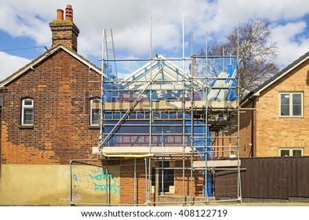 scaffolding, construction or repair of the rural house, fixing facade - stock photo