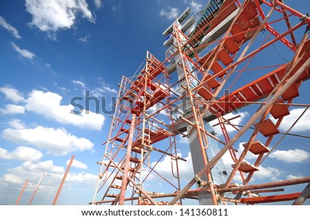 Scaffolding erection at top of building - stock photo