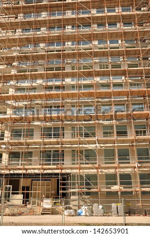 Scaffolding for a newly constructed building during the finishing of the facade - stock photo