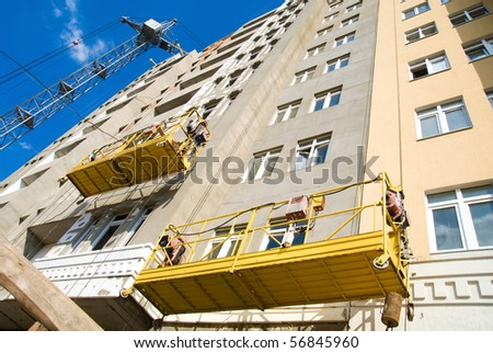 scaffolding hanging on an unfinished building on the background of high-rise construction crane and the blue sky - stock photo