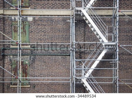 scaffolding ladder against brick wall / industrial background - stock photo