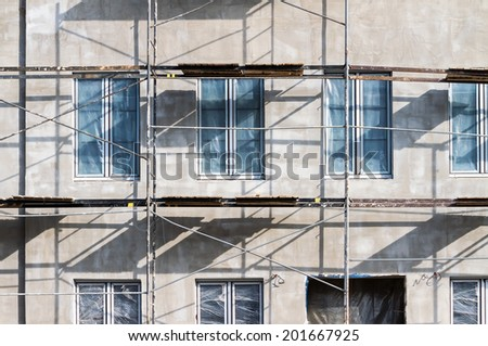 Scaffolding on a building facade used for renovation and construction - stock photo