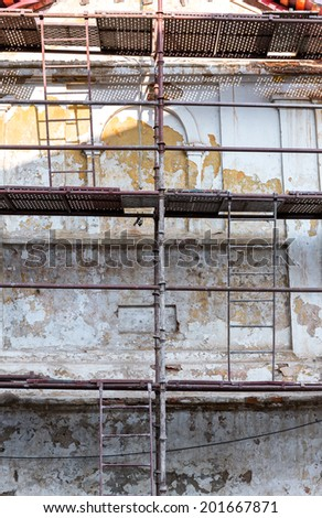 Scaffolding on a building used for renovation old residential building - stock photo
