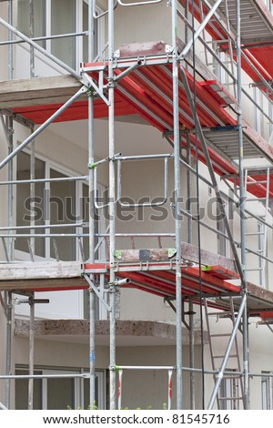 scaffolding on a building wall. building getting a new paint. - stock photo