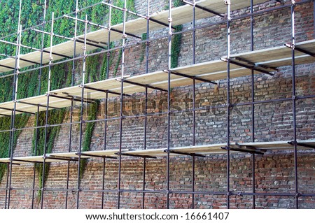 Scaffolding on a wall of the old citadel - stock photo