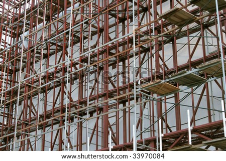 Scaffolding on building exterior. Low angle view at scaffolding on exterior of a city building - stock photo