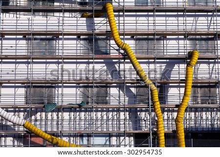 Scaffolding with yellow piping for debris on the white facade of the house to be repaired - stock photo