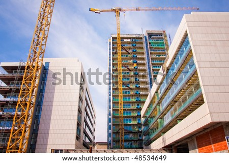 Scaffolds and cranes at buildings construction site - stock photo
