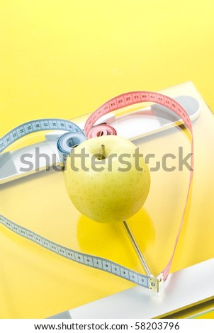 Scale,measuring tape and apple on yellow background - stock photo