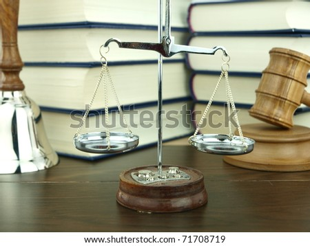 Scale of justice, hand bell and judge's gavel with a stack of legal books background - stock photo