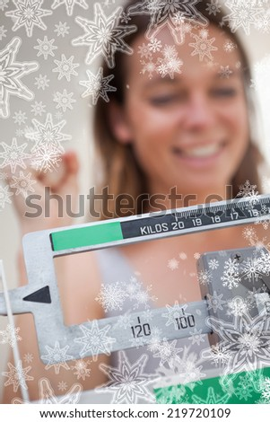 Scale showing dieting success for woman against snowflakes on silver - stock photo