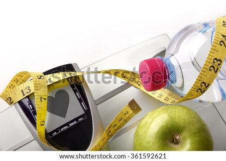 Scale with heart message with mineral water, apple and tape measure isolated. Concept health, diet and nutrition. Horizontal composition. Top view - stock photo