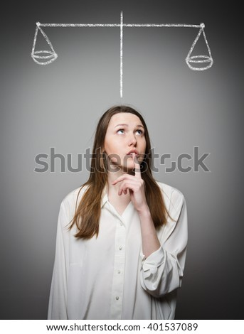 Scale. Young slim woman is full of doubts and hesitation. - stock photo