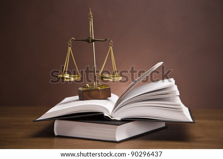 Scales of justice and gavel on desk with dark background