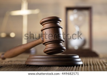 scales of justice, hourglass, gavel, on wooden desk