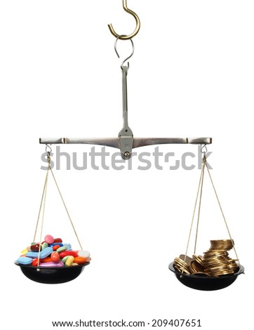 Scales with medicine and golden coins - stock photo
