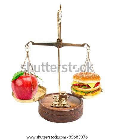 Scales with red apple and a hamburger. - stock photo