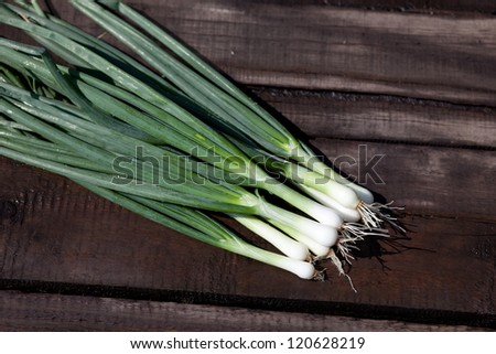 Scallions laying on a wooden table.