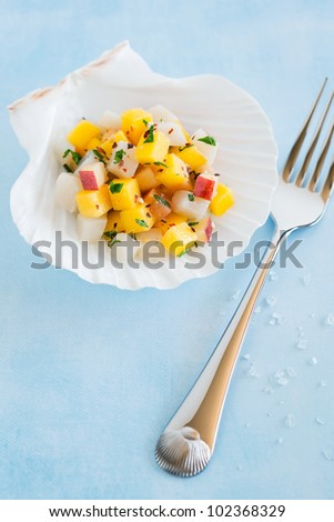 Scallop ceviche with mango and nectarine on scallop shell half, selective focus - stock photo