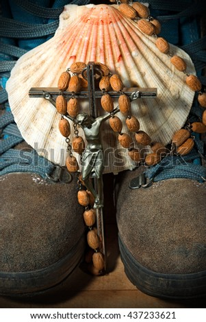 Scallop shell with a wooden rosary beads with a silver crucifix over a pair of hiking boots. Symbols of the Christian pilgrimage - stock photo