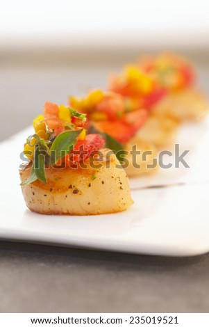 Scallop soaked with fresh yellow mango salsa. - stock photo