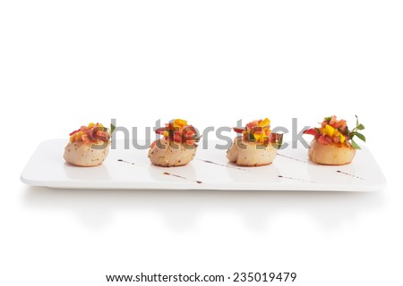 Scallop soaked with fresh yellow mango salsa, isolated on white. - stock photo