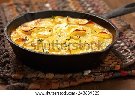 scalloped potatoes in a rustic iron skillet - stock photo