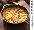scalloped potatoes in rustic iron skillet - stock photo
