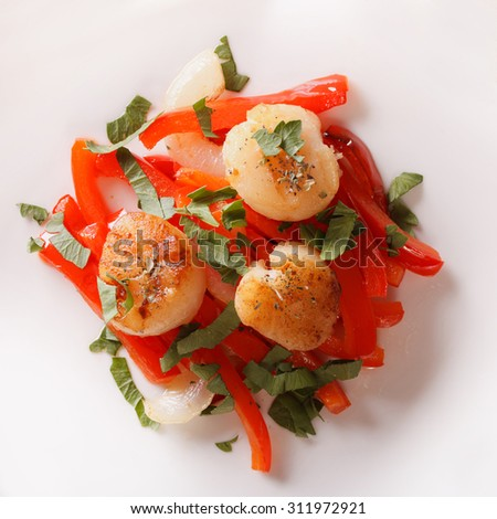 Scallops grilled with peppers on a plate close-up. horizontal view from above