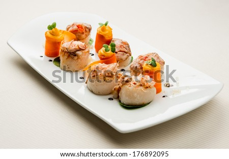 Scallops with salmon roe, crab meat, braised ox roulade, carrot puree and orange tapioca  - stock photo