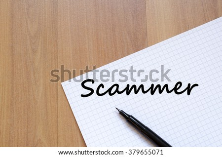 Scammer text concept write on notebook with pen - stock photo