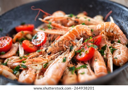 Scampi cooked with tomatoes and parsley - stock photo