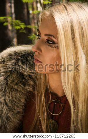 Scandinavian girl with runic signs on a forest background - stock photo